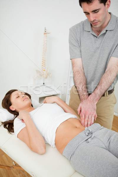 Physiotherapist touching the abdomen of a woman in his office Stock photo © wavebreak_media