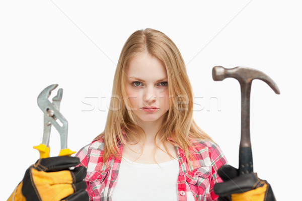 Serious woman holding a hammer and and a wrench against white background Stock photo © wavebreak_media