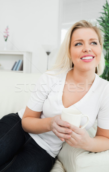 Woman drinking coffee while sitting on a sofa Stock photo © wavebreak_media