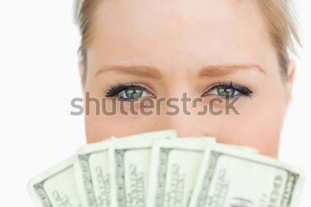 Stock photo: Close-up of a woman face hidden with dollars banknotes against white background
