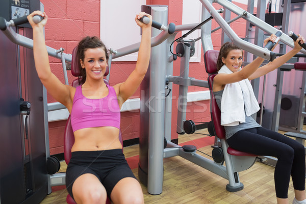 Stock photo: Women using weight machines in gym and smiling