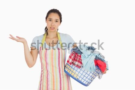 Puzzled look young woman holding laundry basket full of dirty laundry with wrinkled hands  Stock photo © wavebreak_media