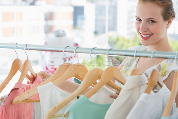 Happy female customer selecting clothes in store Stock photo © wavebreak_media