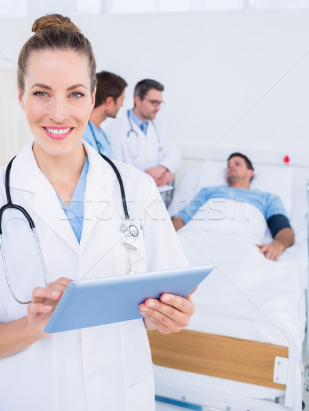 Doctor using digital tablet with colleagues and patient behind Stock photo © wavebreak_media