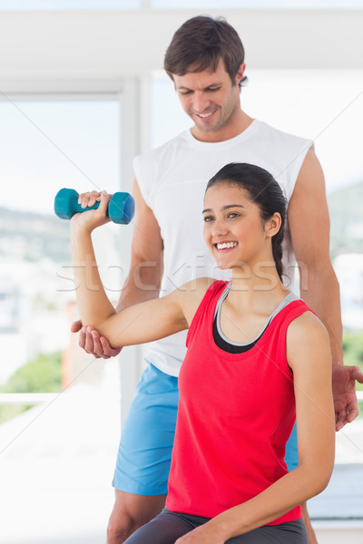 Instructor assisting woman with dumbbell weight Stock photo © wavebreak_media
