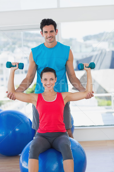 Male trainer helping woman with her exercises at gym Stock photo © wavebreak_media