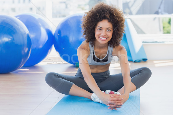 Stock photo: Fit woman doing the butterfly stretch in exercise room