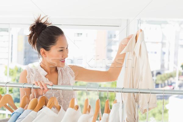 Fashion designer looking at shirt beside rack of clothes Stock photo © wavebreak_media