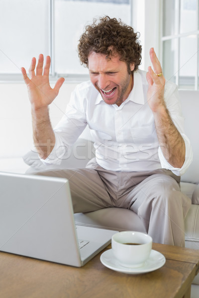 Frustrated man shouting in front of laptop at home Stock photo © wavebreak_media