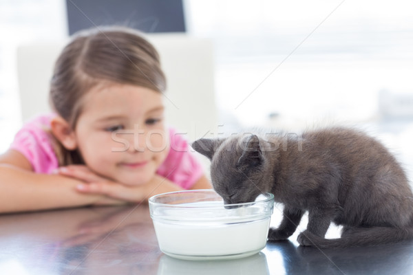 Girl looking at kitten drinking milk from bowl Stock photo © wavebreak_media