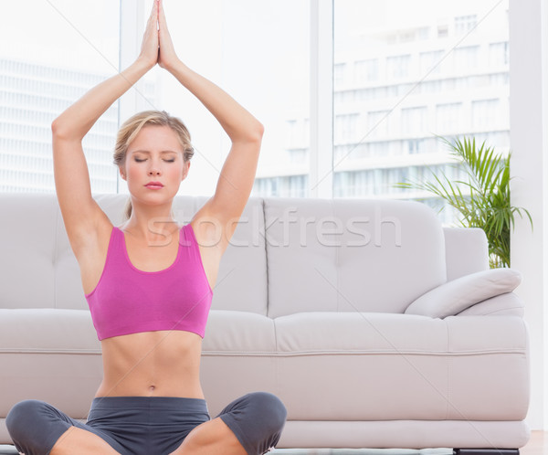 Fit blonde meditating in lotus pose with arms raised Stock photo © wavebreak_media