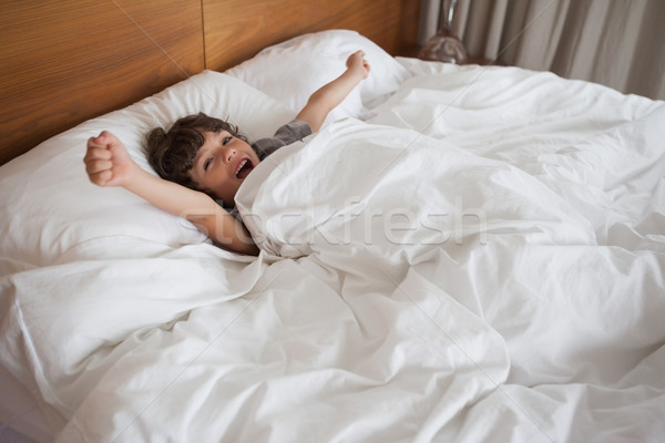 Boy yawning while stretching arms in bed Stock photo © wavebreak_media