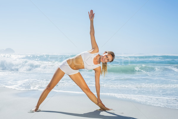 Gorgeous blonde standing in extended triangle pose by the sea Stock photo © wavebreak_media