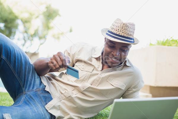 Handsome man relaxing in his garden using laptop to shop Stock photo © wavebreak_media