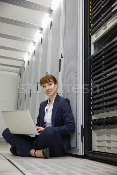 Technician sitting on floor beside server tower using laptop Stock photo © wavebreak_media