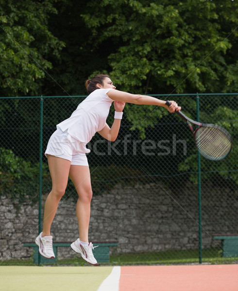 Pretty tennis player jumping and hitting Stock photo © wavebreak_media