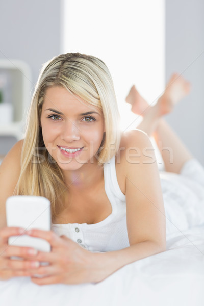 Relaxed beautiful woman text messaging in bed Stock photo © wavebreak_media