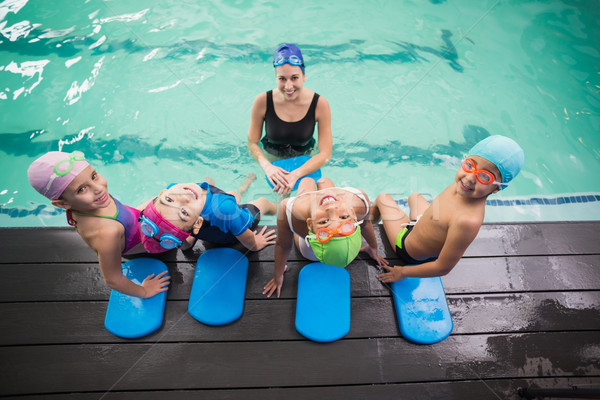 Cute swimming class and coach smiling Stock photo © wavebreak_media