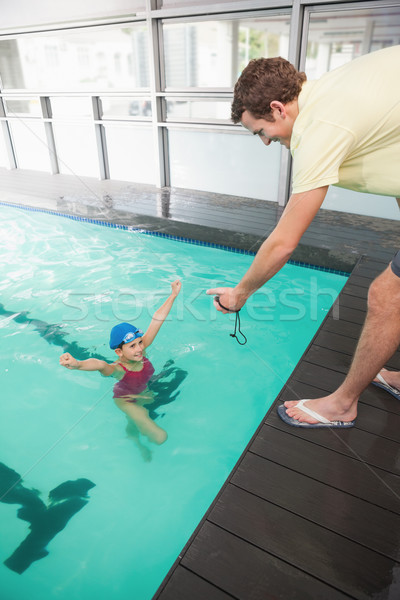 Swimming coach showing time to little girl Stock photo © wavebreak_media