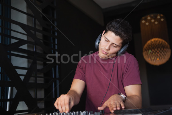 Cool dj working on a sound mixing desk Stock photo © wavebreak_media