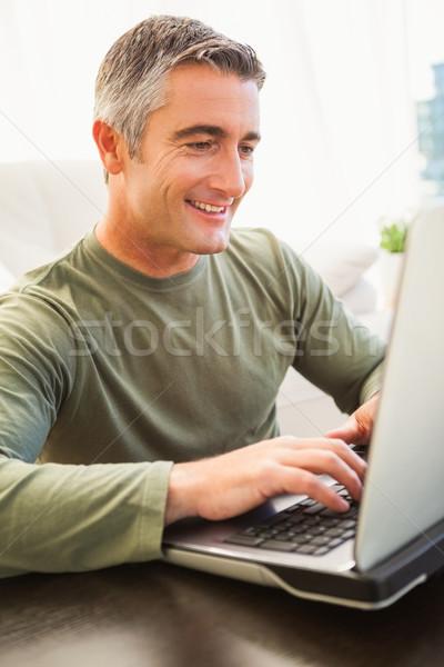 Uśmiechnięty człowiek siwe włosy za pomocą laptopa domu salon Zdjęcia stock © wavebreak_media