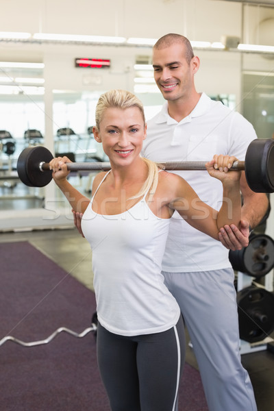 Male trainer helping woman with lifting barbell in gym Stock photo © wavebreak_media
