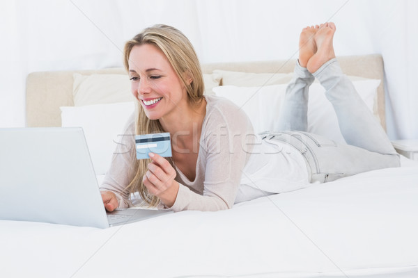 Cheerful blonde shopping online on the bed Stock photo © wavebreak_media