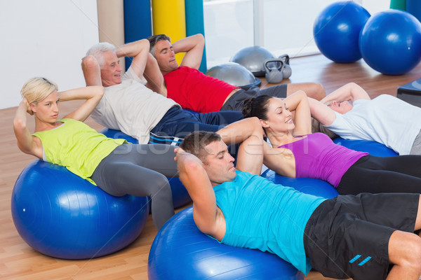 People stretching on exercise balls in fitness club Stock photo © wavebreak_media