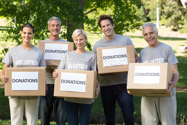 Happy volunteer family holding donations boxes  Stock photo © wavebreak_media