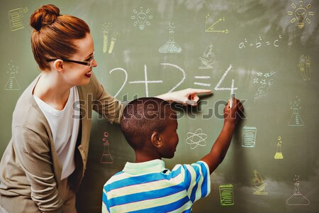 Teacher assisting boy to write on blackboard in classroom Stock photo © wavebreak_media