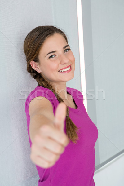 Stock photo: Casual young woman gesturing thumbs up