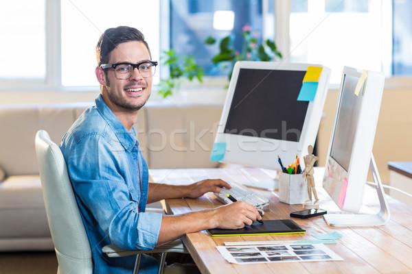 Casual businessman using digitizer at his desk Stock photo © wavebreak_media