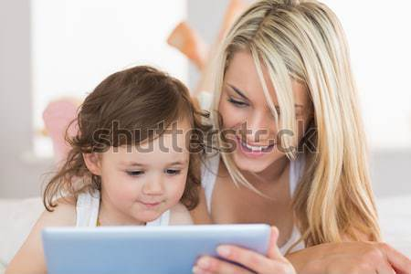 Happy siblings using tablet pc on sofa Stock photo © wavebreak_media