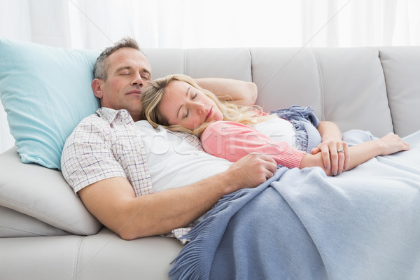Cute couple napping under a blanket on the couch Stock photo © wavebreak_media