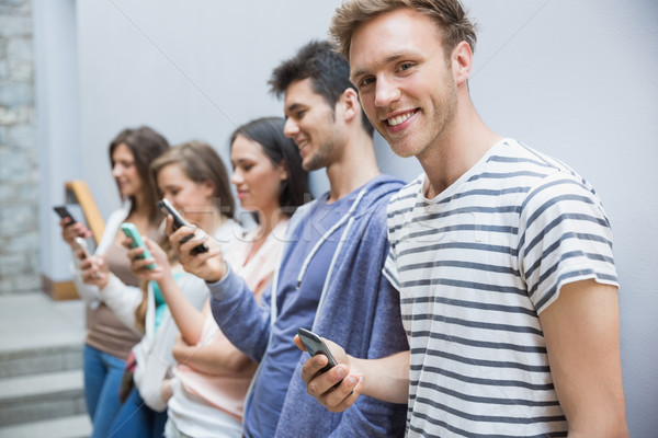 Students using their smartphones in a row Stock photo © wavebreak_media