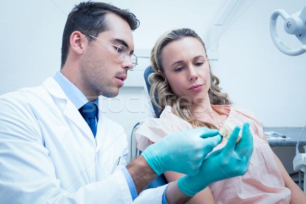 Male dentist teaching woman how to brush teeth Stock photo © wavebreak_media