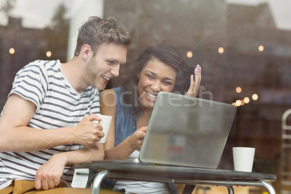 Souriant amis boisson chaude utilisant un ordinateur portable café Université Photo stock © wavebreak_media