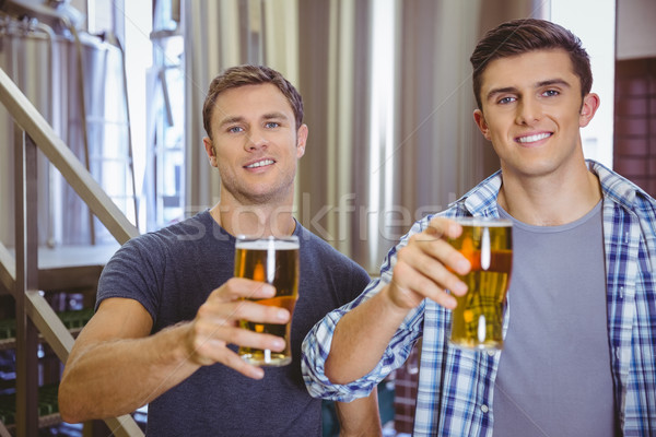 Young men holding a pint of beer smiling at camera Stock photo © wavebreak_media