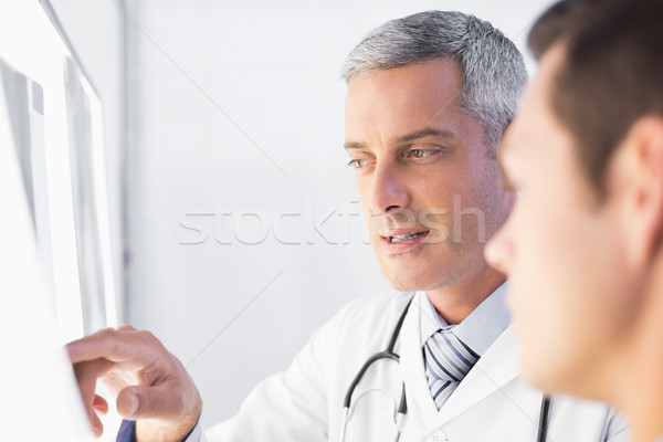 Doctor showing X rays to his patient  Stock photo © wavebreak_media
