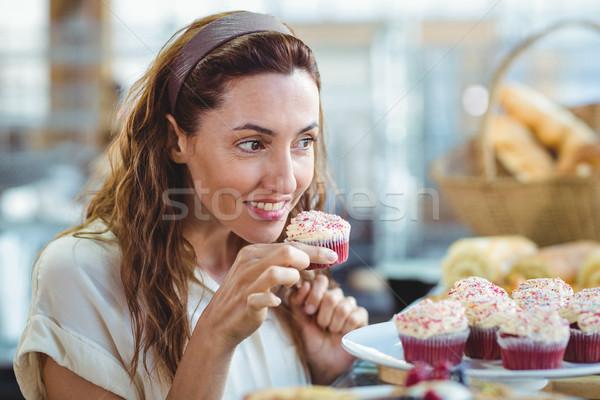 Pretty brunette holding and smelling cupcake Stock photo © wavebreak_media