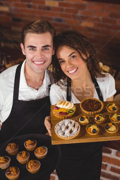 Mosolyog pincér pincérnő tart tálca muffinok Stock fotó © wavebreak_media