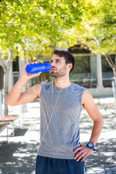 Handsome runner drinking water with hands on hips Stock photo © wavebreak_media