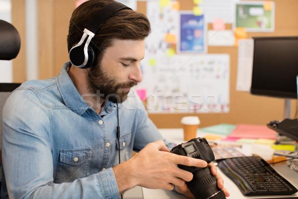 Photographer wearing headphones while using camera in creative office Stock photo © wavebreak_media