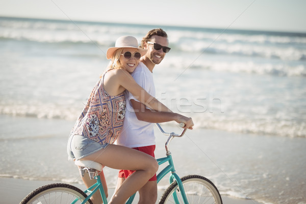 Stock photo: Smiling couple riding bicycle at beach