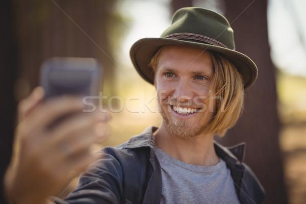 Souriant jeune homme permanent forêt domaine Photo stock © wavebreak_media
