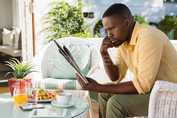Stock photo: Serious young man reading newspaper by breakfast table