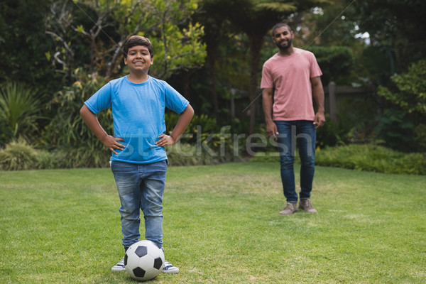 Portrait of smiling boy standing by soccer ball with father at park Stock photo © wavebreak_media