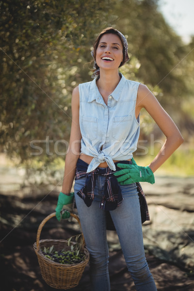 Happy young woman carrying olives in basket at farm Stock photo © wavebreak_media