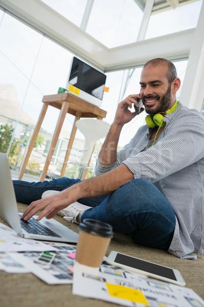мнение дизайнера говорить мобильного телефона используя ноутбук Сток-фото © wavebreak_media