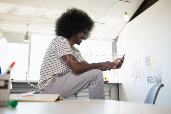 Man using phone while sitting on desk at office Stock photo © wavebreak_media